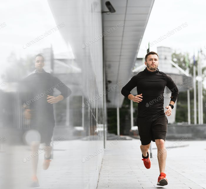 Sporty young guy running in city center in the morning