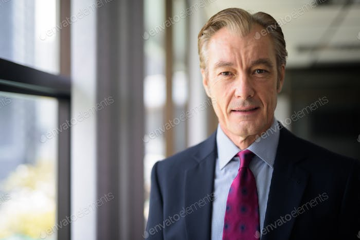 Face of happy mature handsome businessman in suit smiling by the window