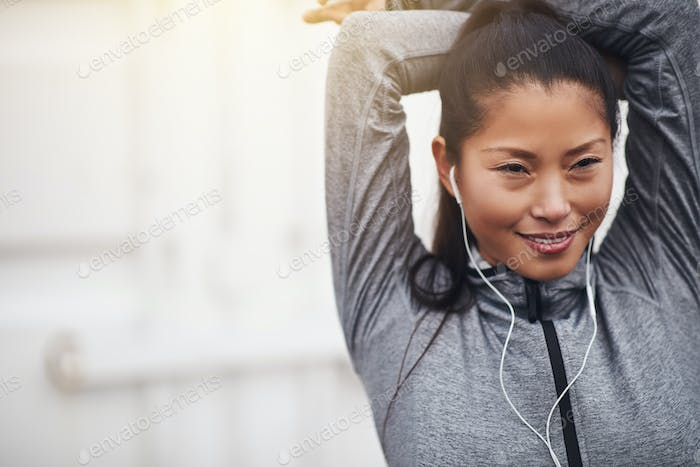Fit young Asian woman stretching her arms before exercising outdoors