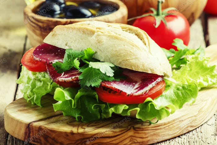 Sandwich in wheat bun with smoked ham, tomatoes and lettuce