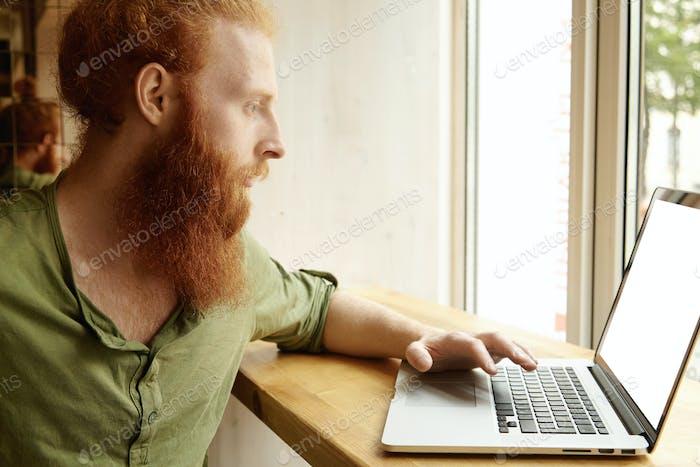 Estudiante guapo con gruesa barba roja trabajando en su papel del curso utilizando la computadora portátil con c