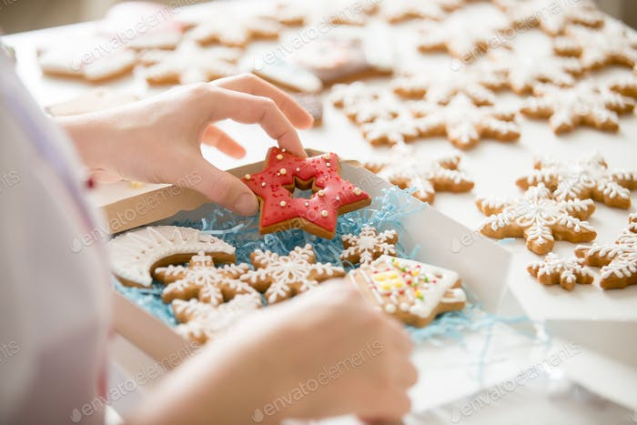 Close up of confectioner hand packing gingerbread cookies into b
