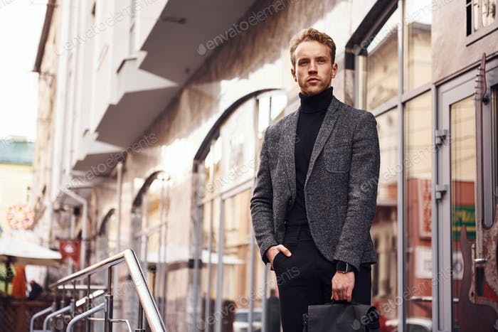 Man in elegant formal wear and with bag is outside against modern building