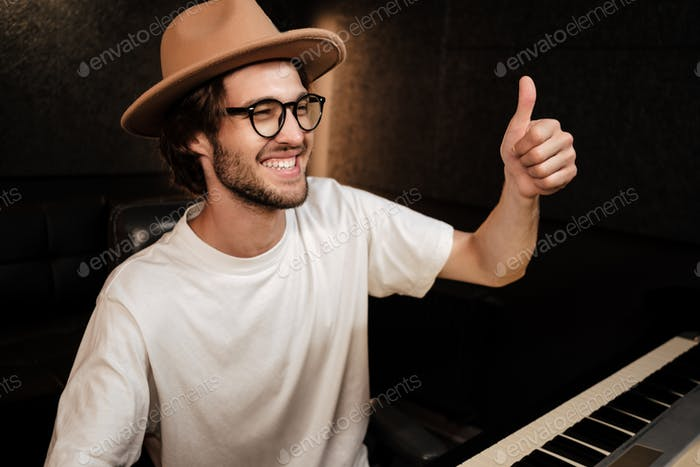 Young stylish musician happily showing thumb up gesture in modern recording studio. Like gesture