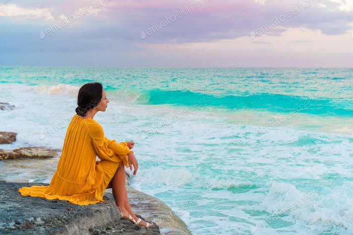 Young beautiful woman in sunset. Happy girl in dress in the evening on the beach