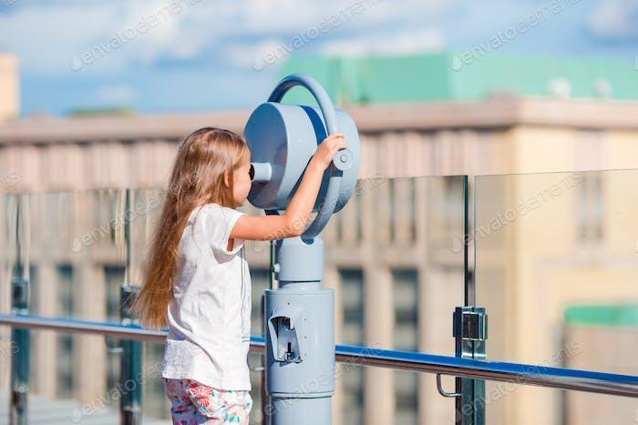 Kleines Mädchen Blick auf Münzfernglas auf Terrasse mit schöner Aussicht