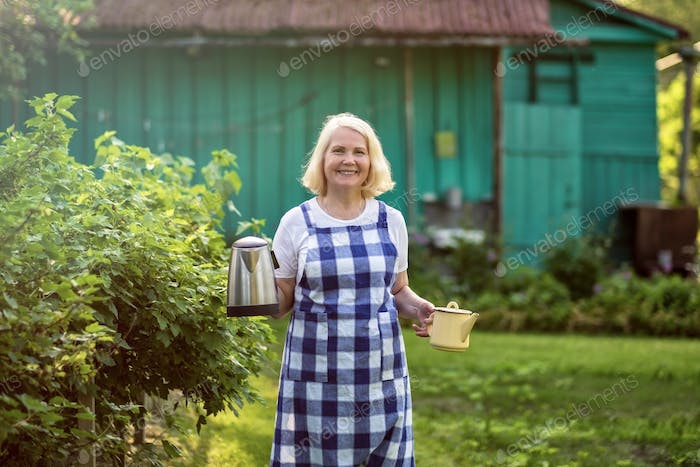 Senior blonde beautiful woman going with teapot to her guests at countryside at her farm.