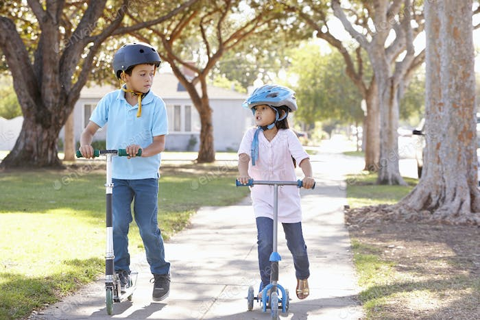 Boy And Girl Wearing Safety Helmets And Riding Scooters