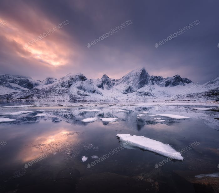 Snowy mountains, blue sea with frosty coast, reflection in water