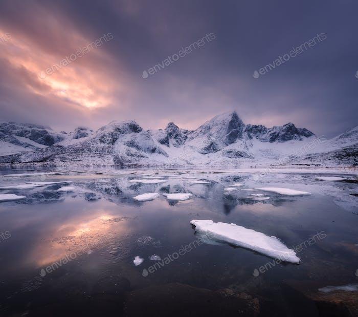 Снежные горы, синее море с морозным побережьем, отражение в воде