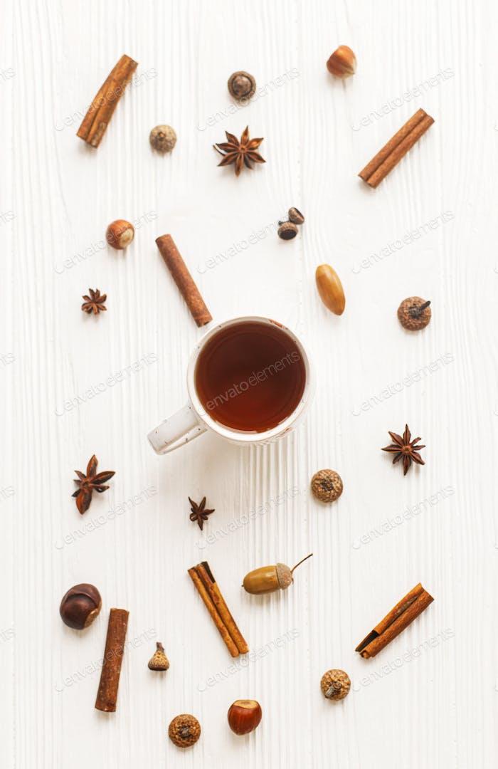 Warm tea, anise star, cinnamon sticks, acorn and nuts on white wood. Autumnal flat lay layout