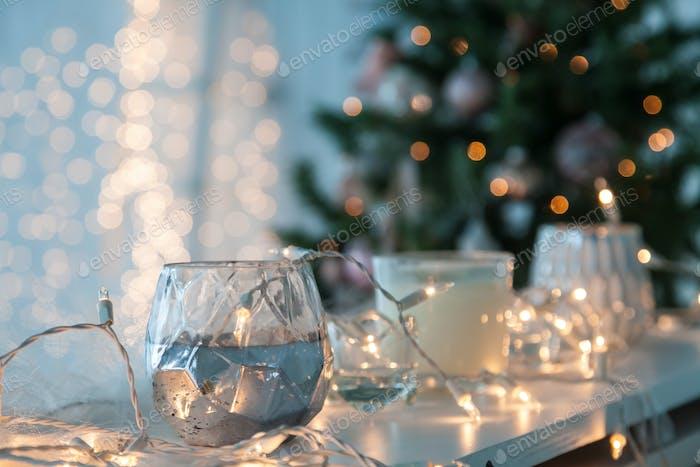 Kerzenhalter mit Weihnachtsbeleuchtung und stimmungsvollem Licht auf Hintergrund