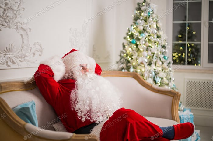 Santa Claus relaxing on sofa against christmas tree at home