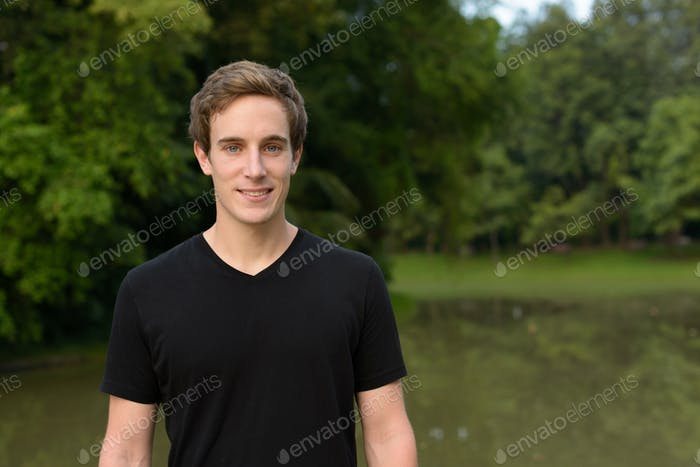 Portrait of young handsome man at the park