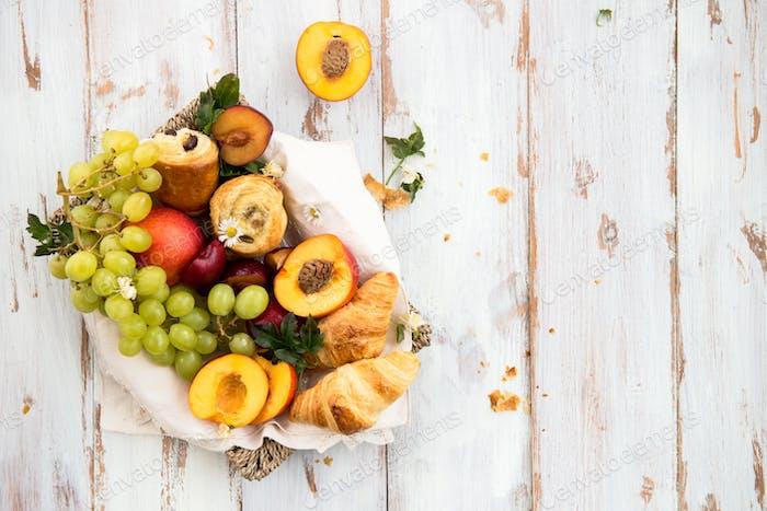 Frühjahrs- oder Sommerkonzept mit Pfirsiche, Pflaumen, Trauben und Gebäck