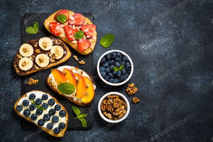Süße Toast-Sortiment mit frischem Obst und Beeren auf schwarz