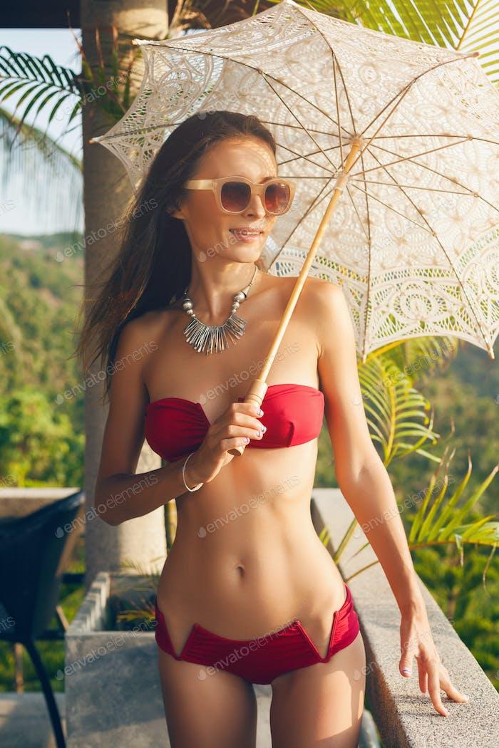 young woman with beautiful slim body wearing red bikini swimsuit holding lace sun umbrella