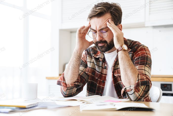 Portrait of young concentrated man thinking while working at home