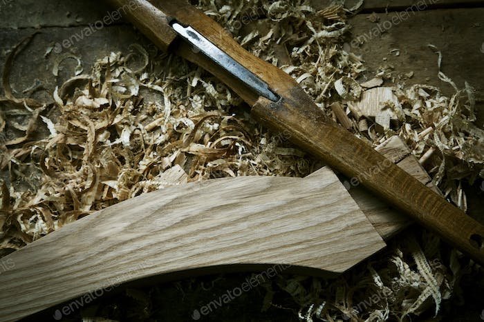 A chisel and wooden object with wood shavings, on a workbench.