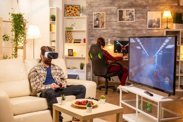 Man gamer using a VR headset to play video games in the living room