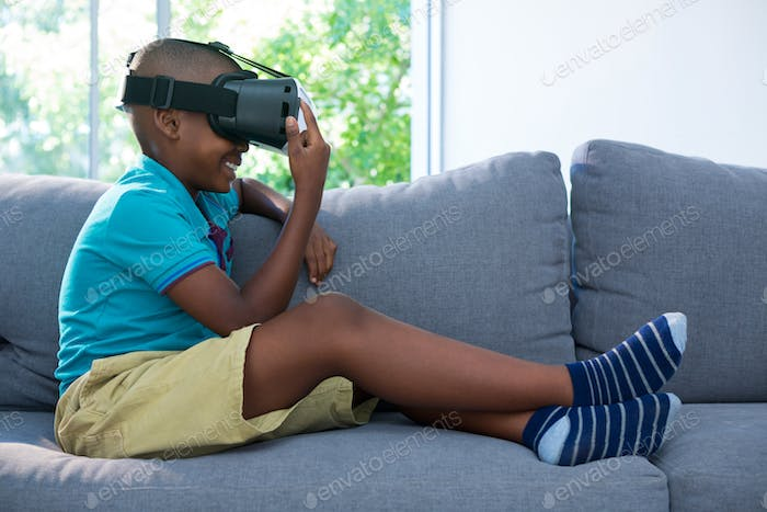 Side view of boy wearing virtual reality headset at home