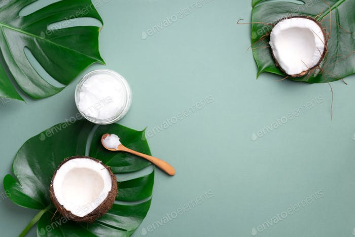 Coconut oil and ripe coconuts, tropical palm and monstera leaves on green background with copy space