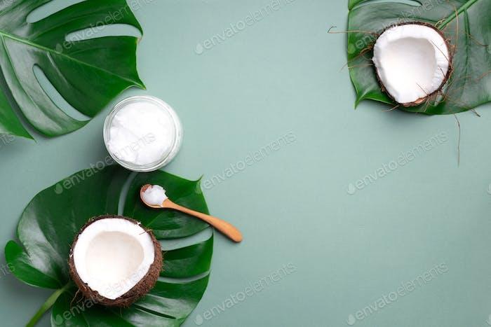 Kokosöl und reife Kokosnüsse, tropische Palmen und Monsterablätter auf grünem Hintergrund mit Kopierraum