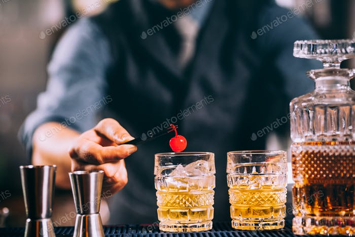 barman preparing old fashioned cocktail, garnishing with cherry. vintage filtered image