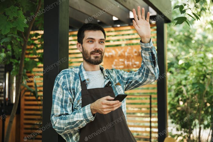 Photo of friendly barista guy smiling while using smartphone in
