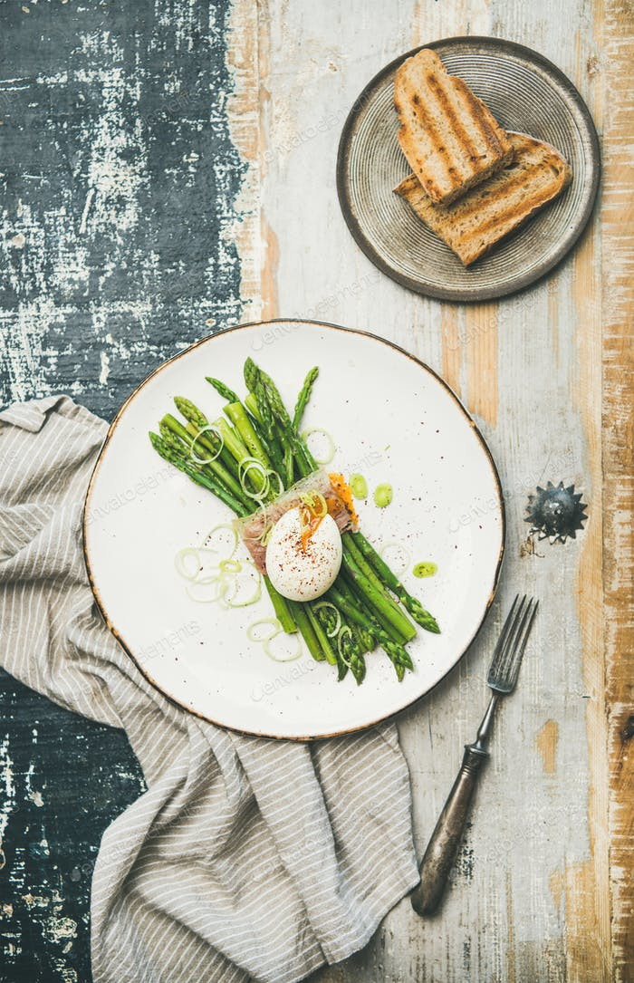 Healthy breakfast with green asparagus, soft-boiled egg , bacon and toasts