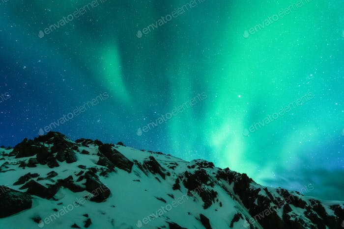 Aurora borealis above the snow covered mountain range