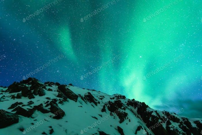 Aurora borealis über der schneebedeckten Bergkette