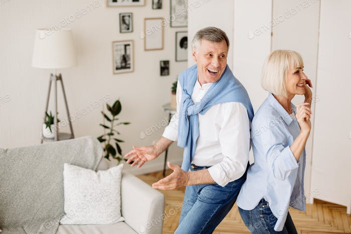Playful mature couple dancing active dance at home