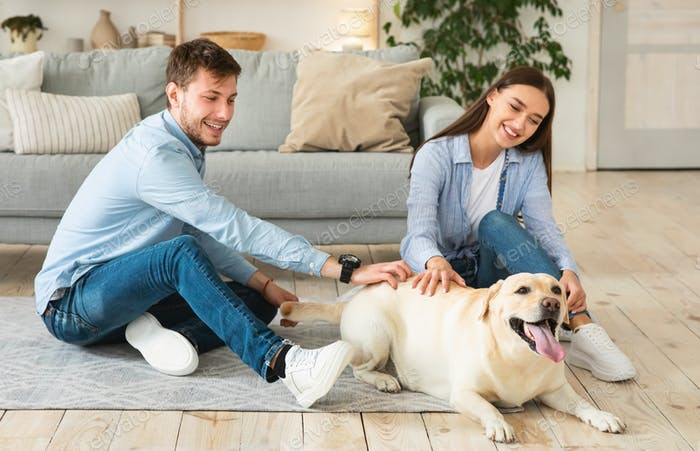 Young family of two people sitting on floor with dog