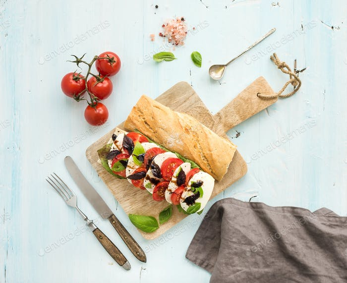 Tomato, mozzarella and basil sandwich on wooden chopping board over light blue background, top view.