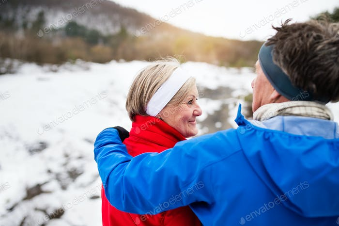 Senior couple jogging in winter nature.