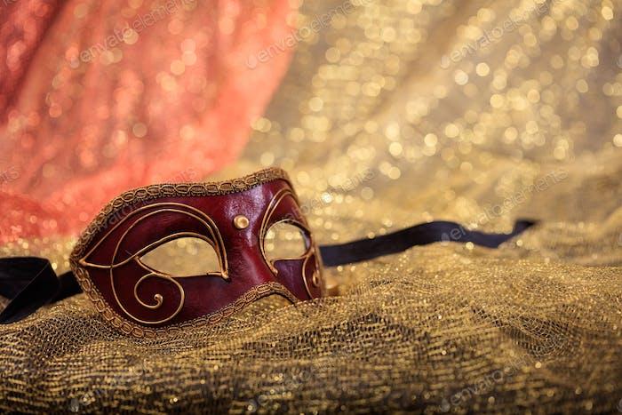 Karnevalsmaske isoliert auf goldenem Unschärfe-Hintergrund