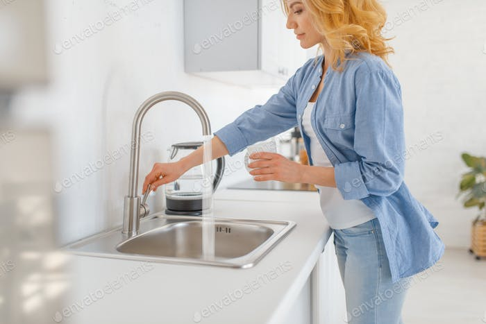 Young woman with glass at the sink on the kitchen