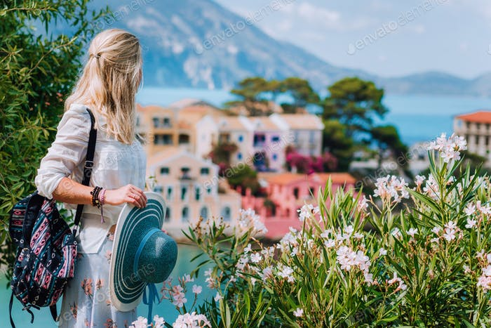 Blond beautiful woman enjoying view of colorful tranquil village Assos on sunny summer travel