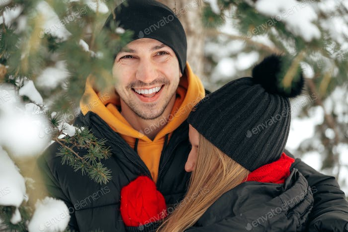 Close up of young couple in warm clothes standing together in a winter park