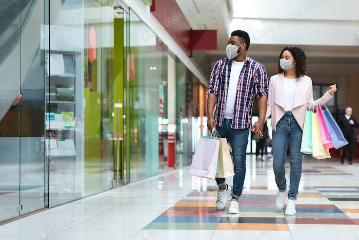 Pandemic Shopping. Black couple in medical masks walking with bags in mall