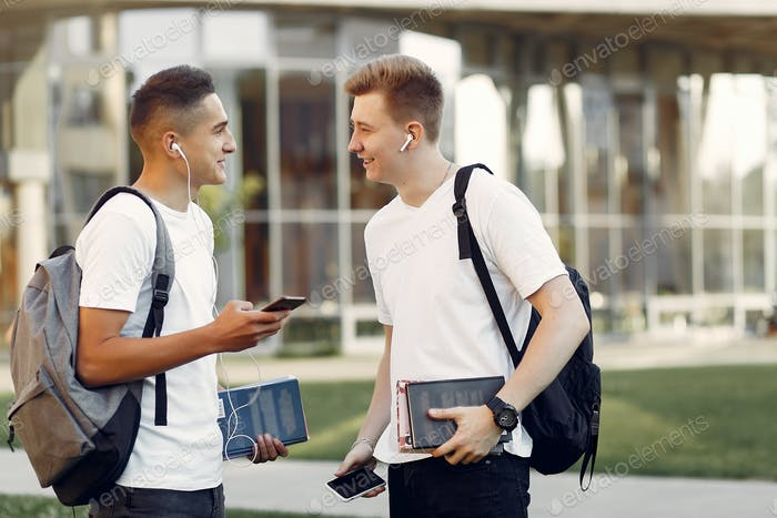 Two students in a university campus with a books