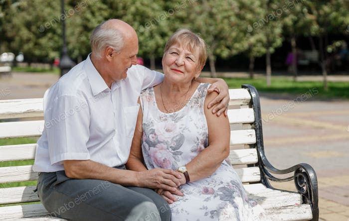 Old man and old woman are sitting lovely together on the bench in a park on a warm day
