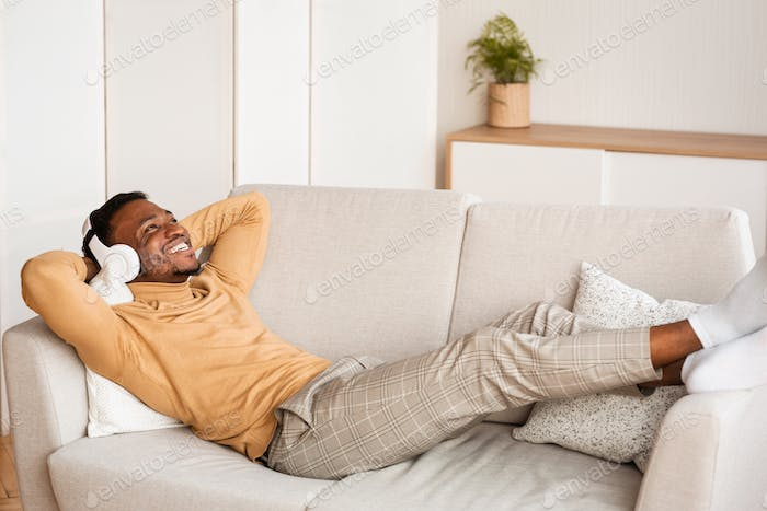 African American Guy In Headphones Lying On Couch At Home