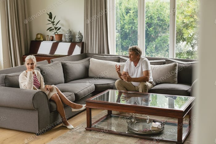 Active senior Caucasian woman ignoring a senior man while arguing on sofa in a comfortable home
