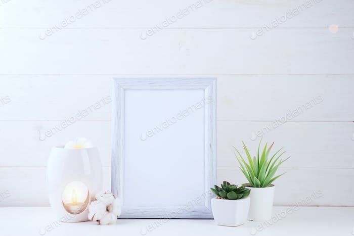 Flowers succulents, candle and aroma lamp with a white frame in the light backgroud, copy space