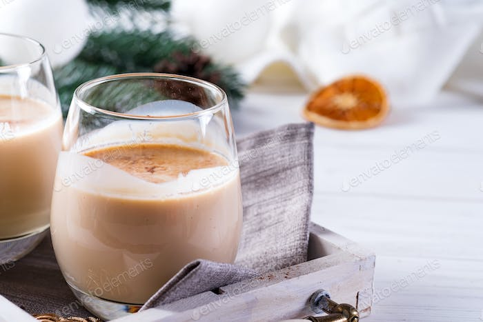 Winter spicy hot drink eggnog in a glasses with cinamon in tray, fir branches on white wooden table