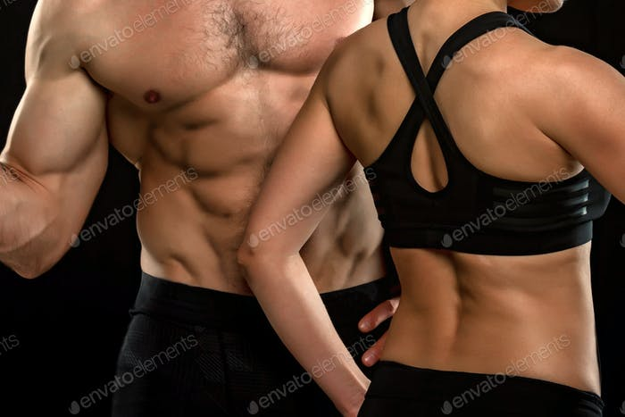 Bodies of male and female fitness model on black background