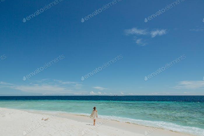 Rückansicht eines Mädchens, das am Sandstrand auf der Insel Thoddoo, Malediven spaziert