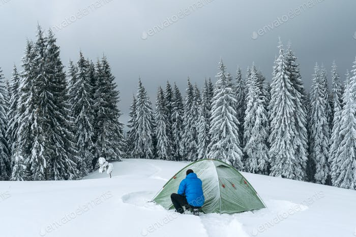 Green tent in winter mountains
